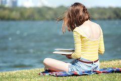 Girl reading a book. At the outdoors royalty free stock photo