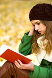 Girl reading book outdoors royalty free stock images