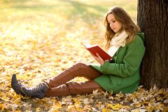 Girl reading book outdoors Stock Photos