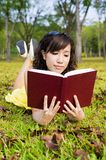 Girl reading book in the outdoors Stock Image