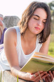 Girl reading book outdoors. Girl laying down reading book outdoors royalty free stock photography