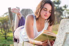 Girl reading book outdoors. Girl laying down reading book outdoors stock images