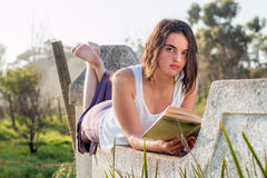 Girl reading book outdoors looking up. Girl laying down reading book outdoors royalty free stock image