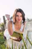 Girl reading book outdoors looking up smiling. Girl laying down reading book outdoors royalty free stock image