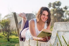 Girl reading book outdoors looking up smiling. Girl laying down reading book outdoors royalty free stock photos