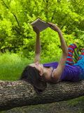 Girl reading a book outdoors. Girl lying on the old tree and looks at the book Royalty Free Stock Image