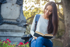 Girl reading book outdoors Stock Image