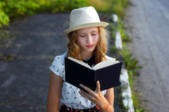 Girl reading a book outdoors.Waiting for the bus. Stock Photo
