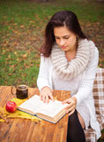 Girl reading a book outside in autumn Stock Images