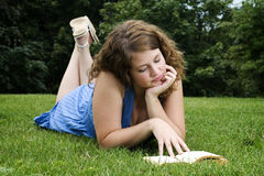 Girl reading book in park. Enjoying summer Royalty Free Stock Photo