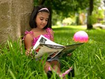 Girl reading a book in the park stock image