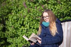 Girl reading a book in the park on the bench Stock Photography