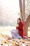 Reading in nature is my hobby,Girl with book and tea in the autumn park. Girl reading a book in a park in china. relax in the middle of nature . autumn leisure Stock Images