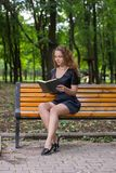 A girl is reading in the park. Stock Photos