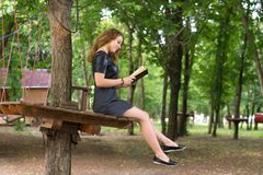 A girl is reading in the park. Royalty Free Stock Images