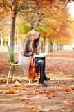 Girl reading a book in park Stock Photography