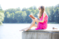 Girl reading a book in  park film effect Stock Photos