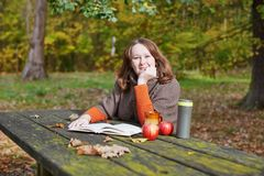 Girl reading a book in park Royalty Free Stock Image