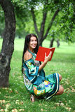 Girl reading a book in the park Stock Photography