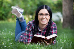 Girl reading book in park Stock Photography