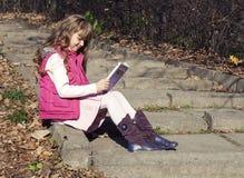 Girl reading book in park Stock Photo