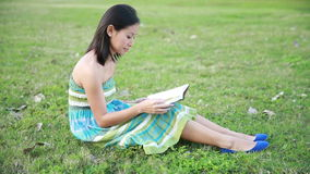 Girl reading book in park smiling stock video
