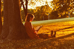 Girl reading book at park Royalty Free Stock Images