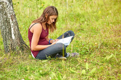 The girl is reading a book in the park in the summer Stock Photo