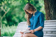 Girl reading a book in park Stock Image