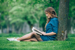 Girl reading a book in park Stock Photo