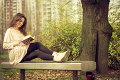 Girl reading a book in park Stock Images