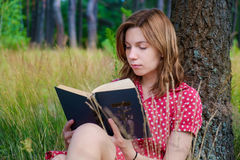 Girl reading a book in the park. Young beautiful girl reading a book in the park Royalty Free Stock Photo
