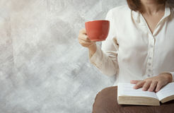 Girl reading a book on pillow and drinking coffee. A Girl reading a book on pillow and drinking coffee. Relax and education concept stock image