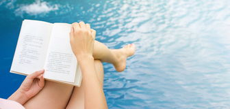 Girl reading a book by the pool. Girl reading a book by the swimming pool. First person Stock Photo