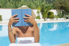 Girl reading a book by the pool Stock Photo