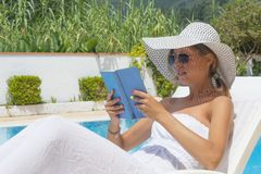 Girl reading a book by the pool Stock Photos