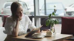 Girl reading book and relaxing in the cafe. girl in business clothes resting during the lunch break Royalty Free Stock Photo