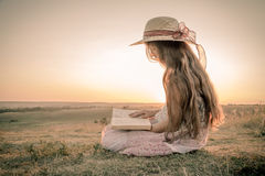 Girl reading the book on rural landscape Royalty Free Stock Photos