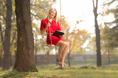 Girl reading a book seated on swing in a park. Joyful girl in a red dress reading a book seated on swing in a park royalty free stock photo