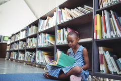 Girl reading book by shelf in library Royalty Free Stock Images