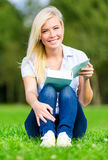 Girl reading book sits on the grass royalty free stock image