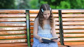 Girl reading a book while sitting on the bench stock video