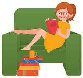 Girl reading a book sitting in a chair Stock Images