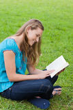 Girl reading a book while sitting down in a park Stock Photo