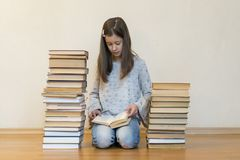 Girl reading a book sitting on the floor in an apartment. Cute girl reading book at home. education and school concept - little royalty free stock photo