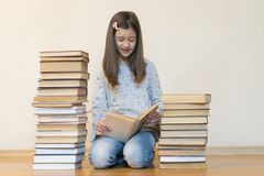 Girl reading a book sitting on the floor in an apartment. Cute girl reading book at home. education and school concept - little royalty free stock photos