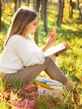 Girl reading a book sitting in the nature with a fallen leaf in Royalty Free Stock Photography