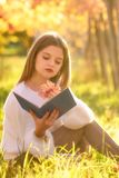 Girl reading a book sitting in the nature with a fallen leaf in Stock Images