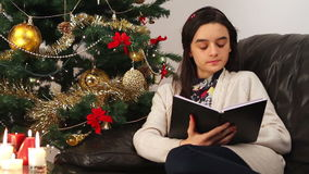 Girl reading a book while sitting near Christmas Tree stock video footage