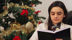 Girl reading a book while sitting near Christmas Tree stock footage